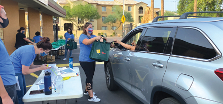 Christina Armold, grants manager for UMOM, helps hand out T-shirts and bags with goodies for people who have registered for UMOM's second annual Scavenger Hunt to End Homelessness (photo courtesy of UMOM).