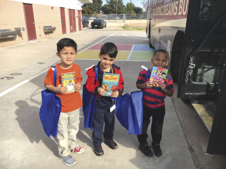 """Children receive donations from the Assistance League of Phoenix's Operation School Bell program. They step aboard a """"department store"""" bus, where they pick out clothes, hygiene kits and books with help from volunteers (photo courtesy of the Assistance League of Phoenix)."""