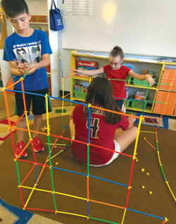 Vincent, Gema, center, and Aubrey, fourth-graders at Midtown Primary School, construct a cube house out of linking sticks as part of a STEAM project for the school's after-school Shazam club (photo courtesy of Midtown Primary School).