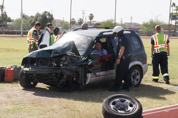 Central High drama student Diana Hernandez gets support from a Phoenix police officer as she is trapped in a wrecked car during a mock DUI crash demonstration.