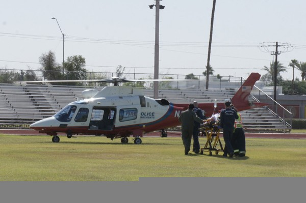 Phoenix Firefighter Curtis Knobbe is taken to the waiting Phoenix Firebird 10 rescue helicopter for transport. A high school student could not be used for this demonstration, so Knobbe volunteered.