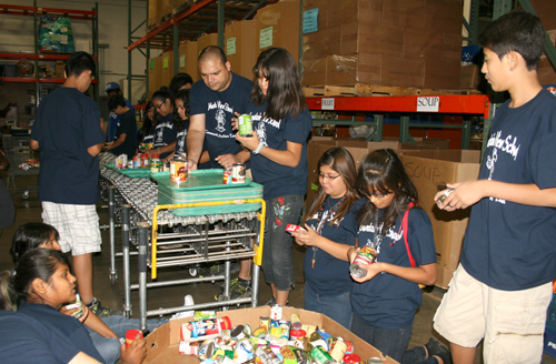 Clockwise from bottom left: Mountain View students Kathy Guzman, Talia Armenta and David Torres, their teacher Julio Valenzuela, and students (center to far right) Lizbeth Damian, Karen Manzares and Augustin Dominguez help sort two tons of food at the Desert Mission Food Bank. The students are part of the Community Action Team on campus (photo by Patty Talahongva).
