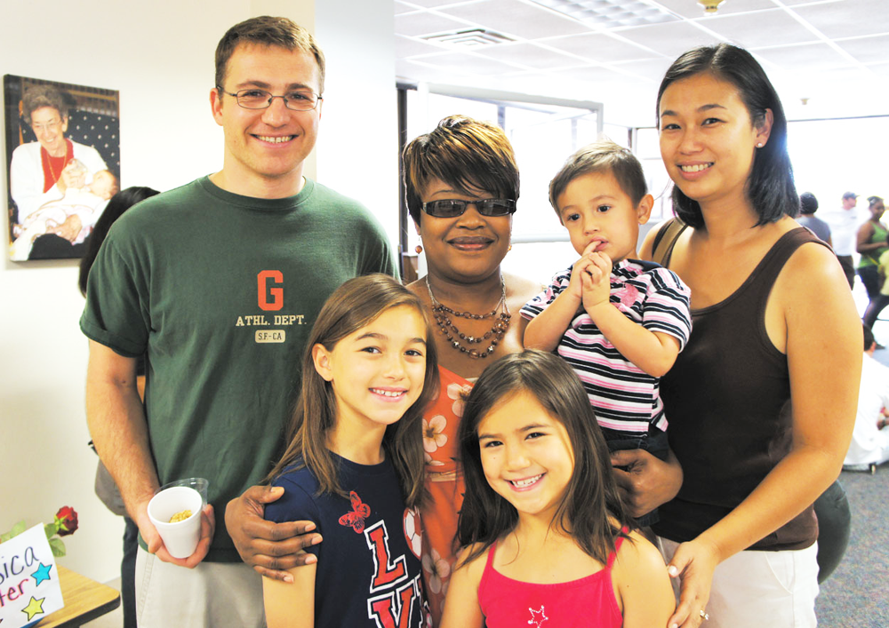 Celebrating their memories of the Beatitudes Agelink Intergenerational Child Development Center are Devisha King (center), who works with the 1- and 2- year olds, and the Feix family (from left), Jeff; Bianca, 10; Mia, 7; Alex, 2, and Teresita. Bianca and Mia both are graduates of King's class, and Alex recently was in King's class as well, but his parents will have to find him a new school when the center closes on July 12 (photo by Teri Carnicelli).