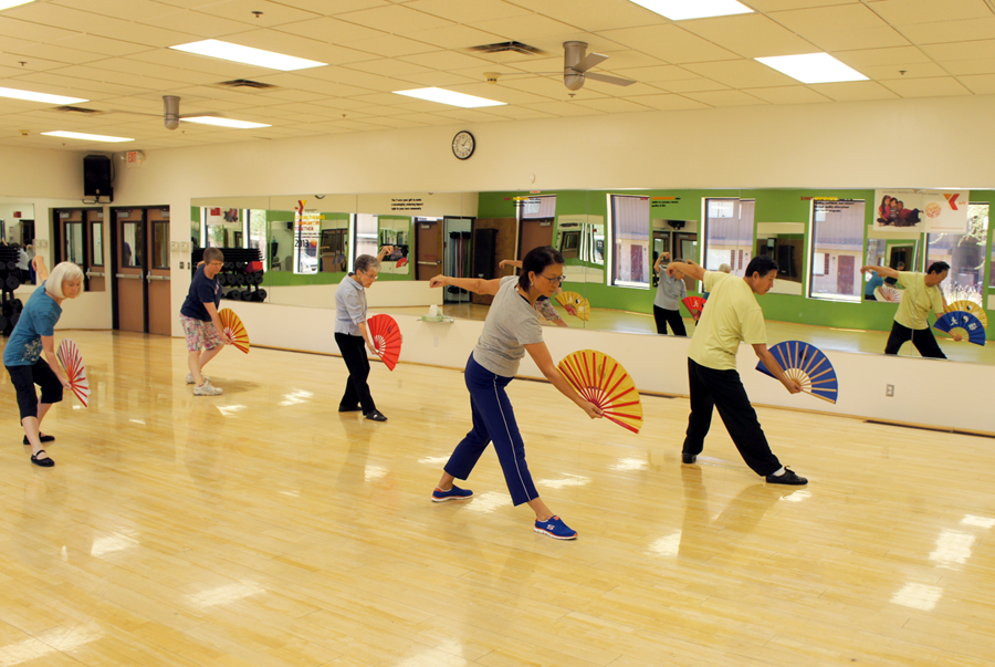 """Practicing the art of """"Kung Fu Fan"""" are Tai Chi Chuan students, from left: Kay Martens, Mandy Patel, Barbara Spear, Cathy Chung, and her husband, Albert, who teaches the class Thursday afternoons at the Chris-Town YMCA (photo by Teri Carnicelli)."""
