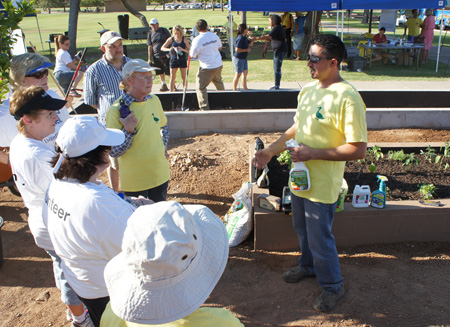 Jeremy Vasquez of Butler Urban Gardens, right, discusses proper garden care and feeding with a group of community residents during the opening day celebration of the new Mountain View Park Community Garden (photo by Teri Carnicelli).
