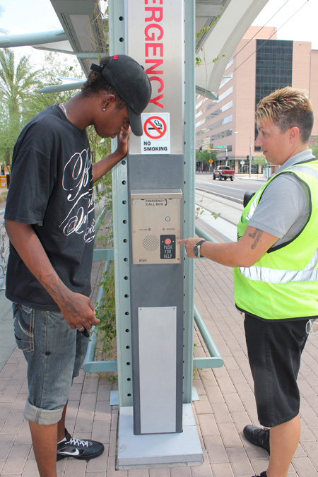 "Light Rail Supervisor Michelle Enciso, right, points out the new ""Safe Place"" emergency button for homeless youth to use for assistance to Doug Criswell, a teen who has been served by the programs at the Tumbleweed Center for Youth Development (submitted photo)."