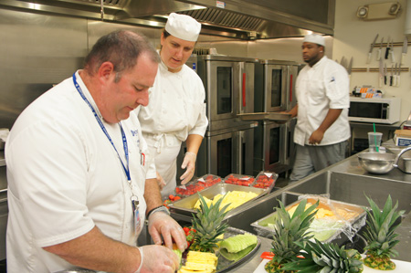Phoenix College Culinary Arts instructor and chef, Joe Kalfus, and student Jaleala Green prepare a fruit platter for a catering order, while student LeVon Pope-Whatley grabs a tray of lamb chops for the afternoon's entrée at Café Oso, the campus' recently remodeled dining area (photo by Teri Carnicelli).