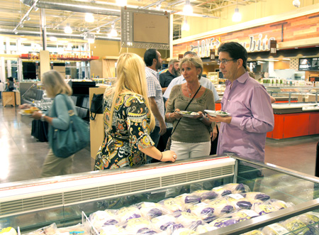 Longtime North Central resident and owner of The Urban Farm, Greg Peterson (right), and Mary Beth Markus, owner of Desert Song Yoga, enjoy fresh sushi and other appetizers while chatting with Theresa Sarna (left) of Whole Foods Market Camelback during the community preview night of the new store, held on Sept. 16 (photo by Teri Carnicelli).