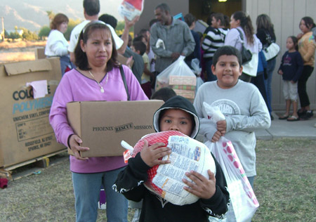 A woman and her two sons happily carry their food box, frozen turkey and donated Christmas gifts given to them through the Phoenix Rescue Mission's holiday help programs (photo courtesy of the Phoenix Rescue Mission).