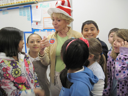 Kids surround Bonnie Murphy, BookPAL, after she reads at Camelview Elementary during Read Across America Day (submitted photo).