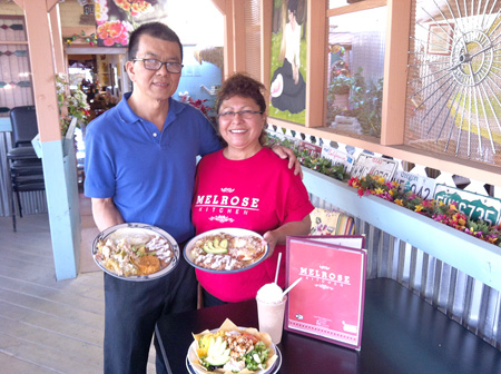 Boonchai Siriswangporn and his wife, Martha Mendoza, stand in their redecorated patio and present new breakfast items. He's holding the Chicken Chilaquiles and she has the Huevos Rancheros. On the table is a new lunch item, Chicken Taco Salad, and an Iced Mocha (photo by Patty Talahongva).