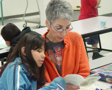 Volunteer tutor Freddie Lieberman works with Paige, a student at Madison Heights, as part of the OASIS tutoring program. The next volunteer orientation is set for Jan. 27-29 (submitted photo).