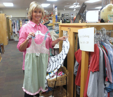 Susan Bietau, Assistance League of Phoenix (ALP) volunteer, shows off a few items from the organization's Thrift Shop on 7th Street. Bietau is a resident of North Phoenix and regularly volunteers in the Thrift Shop (photo courtesy of ALP).