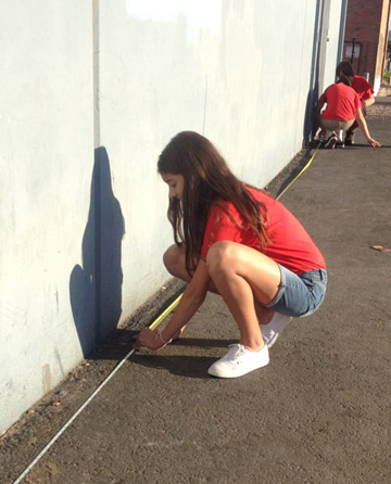 Students from the Madison Meadows National Junior Honor Society measure the outside of the ICM Food and Clothing Bank in downtown Phoenix. Students have taken on an ambitious goal for their Semester of Service project: paint the entire exterior of the building, and replace the rusted gutters and downspouts (submitted photo).