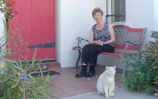 CAPTION IS: G.G. George and her cat, Snowball, sit in front of their historic home in Phoenix's Encanto-Palmcroft Neighborhood. George recently co-authored a book about the history of this area, which in 2002 was named one of the 10 best places to live, out of a pool of more than 1,200 American cities, by Money Magazine (photo by Allison Walker).