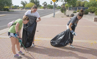 Picking up trash as part of the monthly Sunnyslope Graffiti Fighters volunteer group are, from left, Sunnyslope High School junior Emily Campagnolo and sophomores Emily Westfall and Jasmine Torres (photo by Teri Carnicelli).