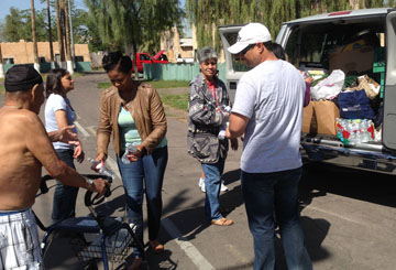Volunteers with Phoenix Rescue Mission's Hope Coach hand out heat-relief items, including bottled water, to members of the homeless community during the summertime (photo by Cliff Danley).