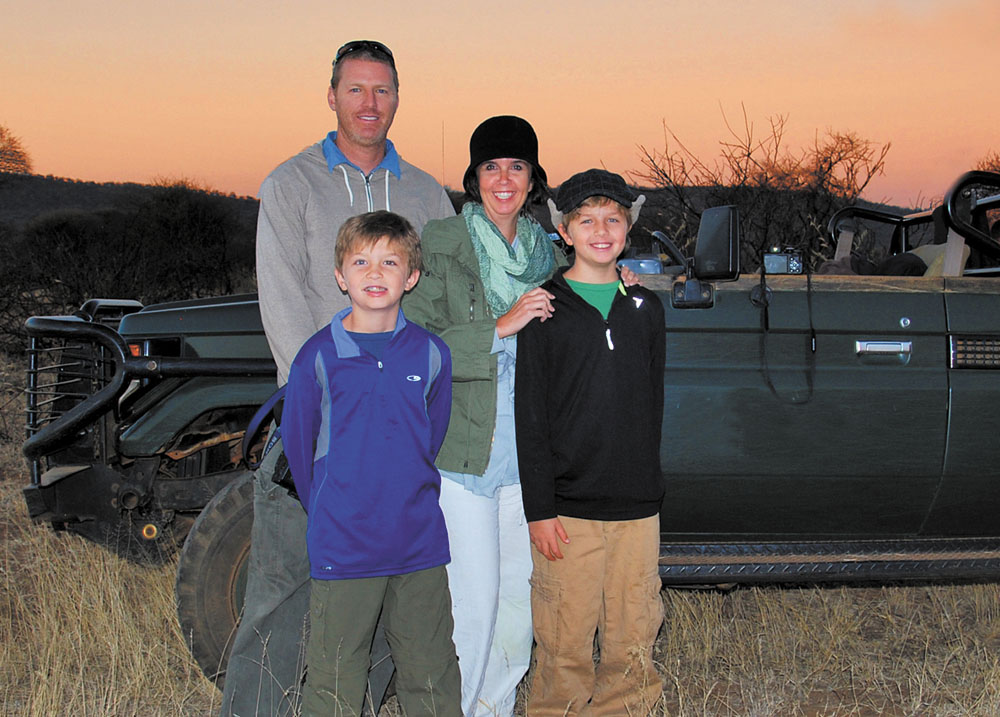 Enjoying a spectacular sunset at the Madikwe Game Reserve in South Africa are the members of the globe-trotting Simmons family, clockwise from top left: dad Jeremy, mom Carrie, and sons Nathan and Seamus (photo courtesy of Travel With Kids).
