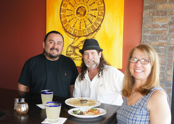 "Obed De la Cruz, left, visits with Mejico customers Rick and Jacque Berry, who are enjoying the happy hours specials: $5 skinny margaritas, $3 cheese quesadilla, $1 carne asada street tacos, and a $3 ceviche tostada which the couple gave ""two thumbs up"" (photo by Teri Carnicelli)."