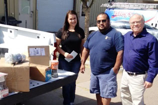 Katie Smith, program director for the Foundation for Senior Living Home Improvements, happily accepts a donation of money and evaporative cooler parts from Ken Goodrich and Dan Burke from Goettl Good Guys Air Conditioning Repairmen (submitted photo).