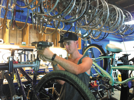 David Claffey repairs a bike in his new shop, started in honor of the memory of his twin brother, Kyle, who passed away last year from a brain tumor. Besides selling used bikes and doing bike repairs, David and other volunteer staff members of the shop also can assemble your new bike purchased elsewhere (photo by Patty Talahongva).