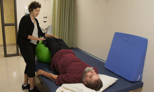 Denise Kriese, a physical therapist at Circle the City Medical Respite Center, works with client David on strengthening his core area after David suffered an injury while homeless in Phoenix (photo by Teri Carnicelli).