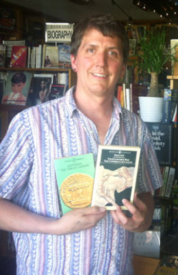 Sven Rosckowff holds up copes of two books he sent to an inmate in Nevada. His store, The Bookshop, offers this service for just the cost of shipping and handling (photo by Patty Talahongva).