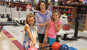Zoe Staten, 6, Arissa Staten, 8 and grandmother Rosie Trujillo enjoy the Kids Bowl Free program at Let it Roll Bowl and Entertainment, ongoing through the end of October (photo by Teri Carnicelli).