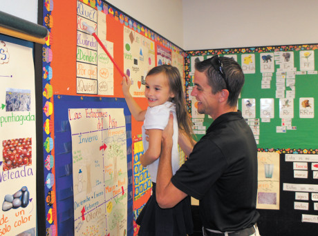 Alannah Monfred, 7, shows dad Robert Monfred her skills in Spanish during an open house inside dual-language teacher Nancy Leon's first-grade class at Madison Heights (photo by Teri Carnicelli).