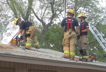 Firefighters from Phoenix Fire Station 11 cut holes in the roof of a vacant home near 38th Street and Indian School road as part of a training opportunity provided Green Street Communities Inc., which will be redeveloping the 3-acre property into 15 new single-family homes (photo by Kira Hamlin of Green Street Communities Inc.).