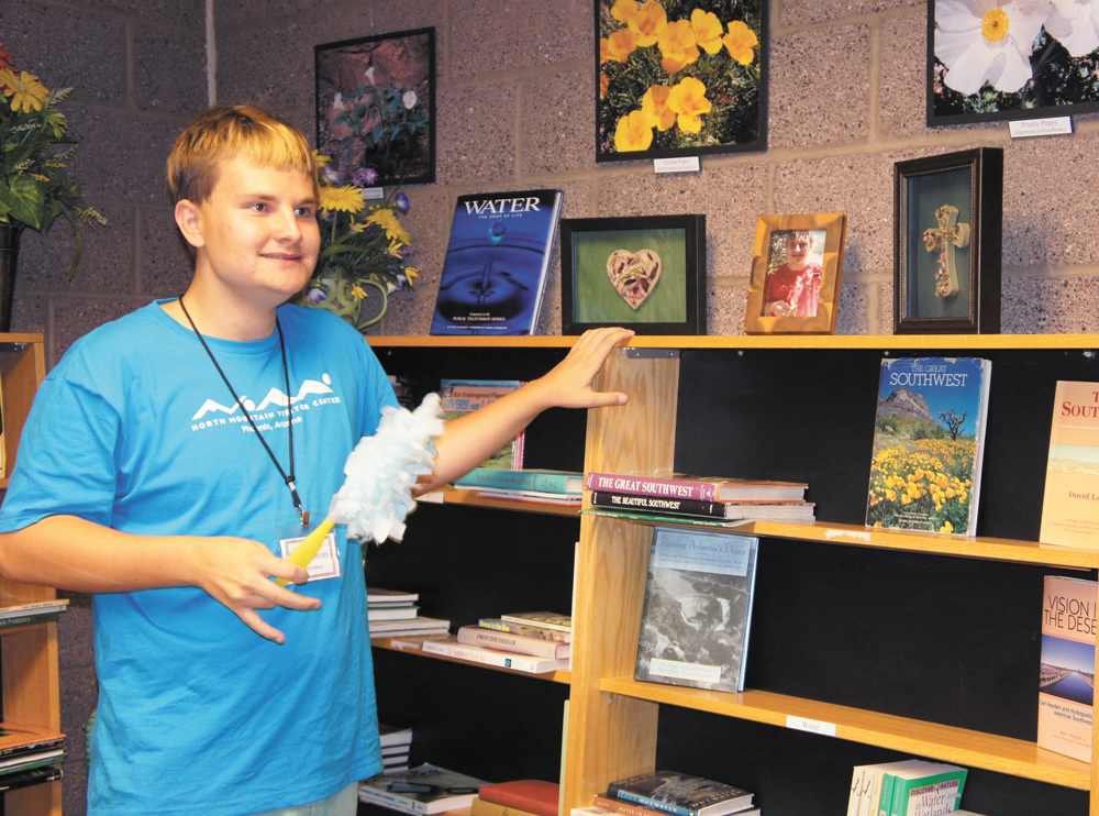 Garrison Mais, 17, dusts the shelves in the library and reading room at the North Mountain Visitor Center, where he's volunteered for over a year. The top shelf also displays a framed photo of Garrison, with two pieces of his original artwork, also framed, on either side of his picture (photo by Teri Carnicelli).