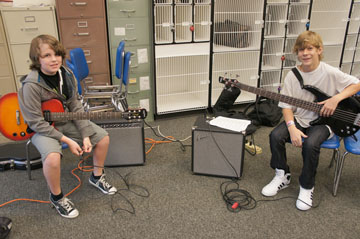 Madison No. 1 eighth grader Collin McShane, left, and seventh grader Josh Weide plug into the new Fender amplifiers that the band department received through a grant from Fender. Collin is also playing one of the new electric guitars also received through the grant (photo by Teri Carnicelli).