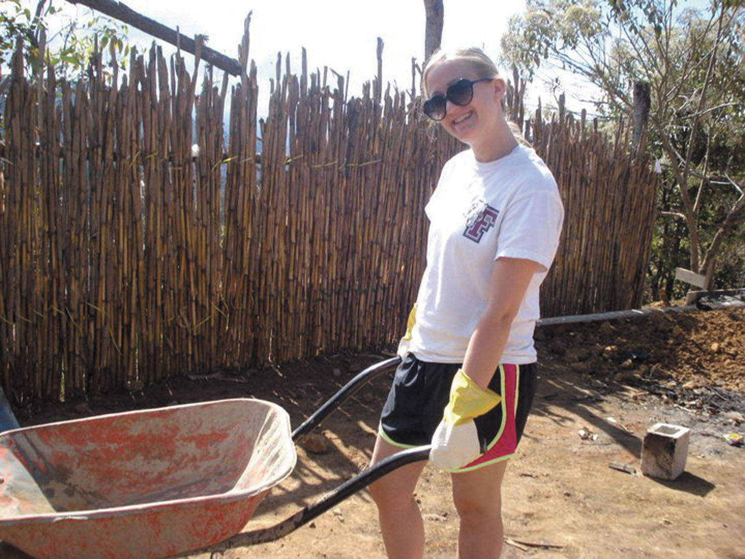 North Central native Catherine Landry grabs a wheelbarrow to help move mixed concrete inside a building to lay a floor down for a rural school during a service trip in Chipocolaj, Guatemala. She traveled there with a group from Fordham University in 2011 (photo courtesy of Cathy Landry).