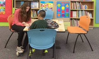 Lauren Scardello helps a child with his homework at the Saint Vincent de Paul Dream Center as part of her Make A Difference Day project (photo by Peter Scardello).