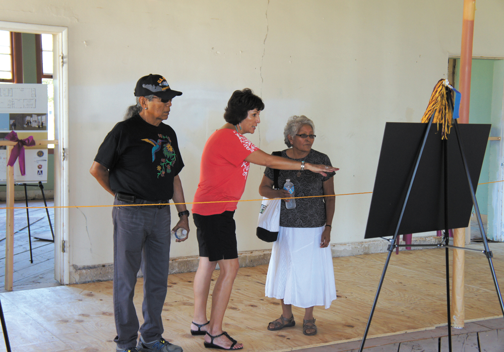 Lana Barrett, center, a volunteer with Native American Connections, explains plans for renovating the old band building at what was once the U.S. Industrial Indian School. Taking a tour of the building are former Indian School band students Leon Nuvayestewa Sr. and his wife, Evangeline, both of whom graduated in 1959 (photo by Teri Carnicelli).