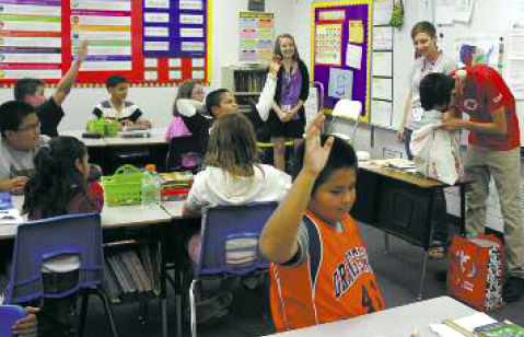"""Fifth-grade students at Orangewood Elementary School try to guess some of the items found inside an """"emergency pillowcase"""" during a presentation by AmeriCorps members assigned to the Red Cross Grand Canyon Chapter. Searching the bag for items guessed by students is Eduardo Camacho, while fellow presenters Jannika Pinter (center) and Rochelle Dashney (left) look on (photo by Teri Carnicelli)."""