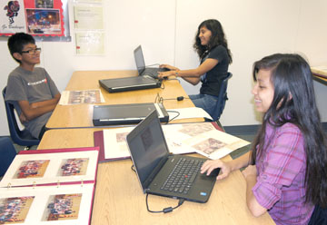 Scanning old photos from the Madison Elementary School District for upload to a new website are Digital Media students from Madison Highland Prep, clockwise from left: Kenny Juarez, Viviana Reyes and Crystal Grier (photo by Teri Carnicelli).