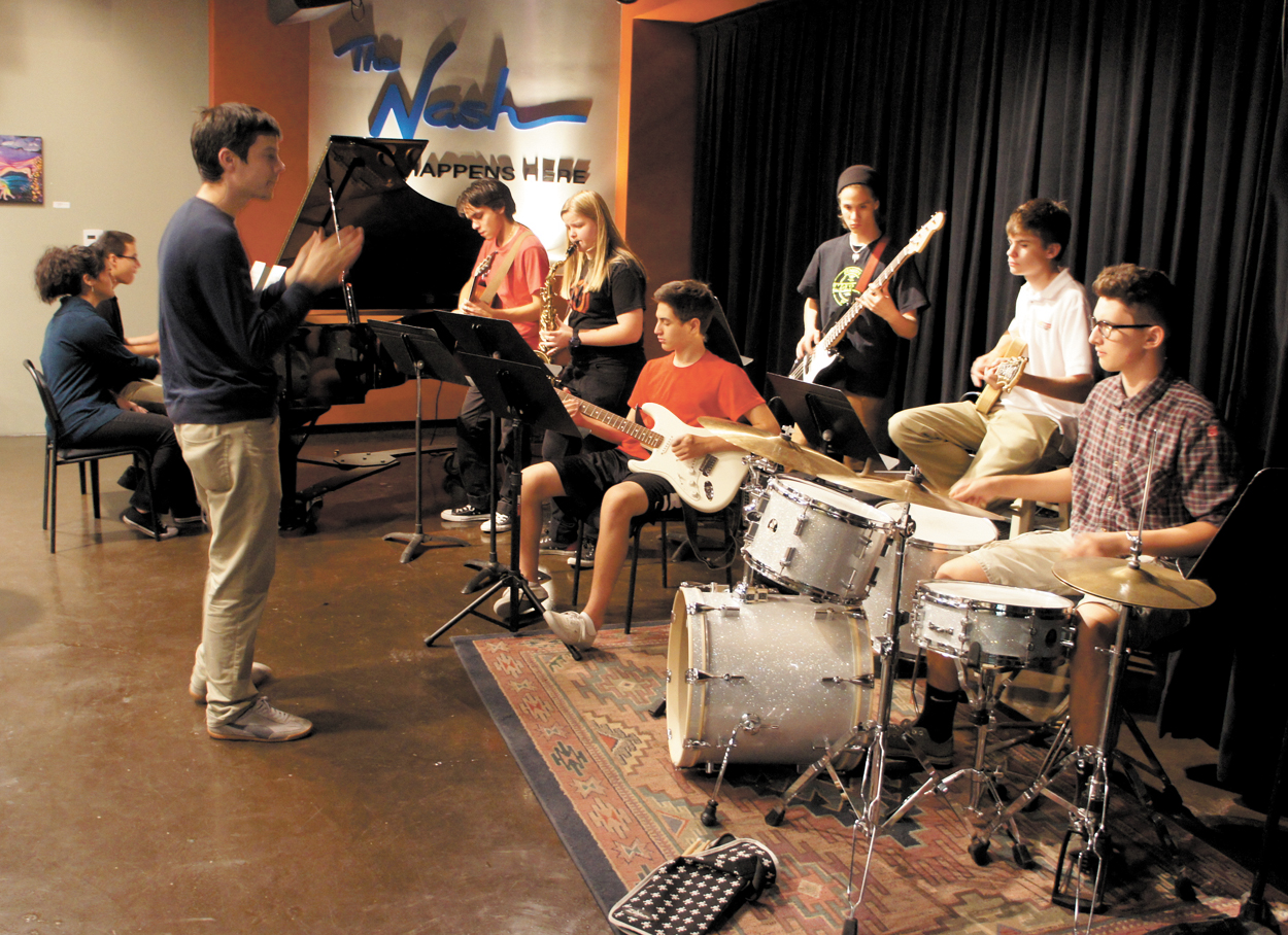 Will Goble keeps time as students from Phoenix Conservatory of Music's Jazz Ensemble rehearse at The Nash in downtown Phoenix. Students include, from left: Angelina Avila and Kiernan Johnson on piano; Omar Torres on acoustic guitar; Elena Rogers on tenor sax; Jude Poorten on electric guitar; Elijah Krueger on bass; Joshua Jacobsen on electric guitar; and North Central resident Cian Callahan on drums (photo by Teri Carnicelli).
