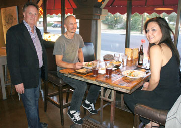 Tim Perkins, owner of Urban Taco, chats with first-time customers Ryan King and Anna Medina, who are enjoying the happy hour specials, which include $1.50 street tacos. If you're feeling adventurous, try the octopus (photo by Teri Carnicelli).