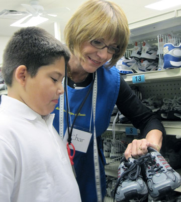 Assistance League of Phoenix volunteer Char Lewis helps a young man pick out a new pair of tennis shoes at ALP's Philanthropic Center. ALP's largest program, Operation School Bell®, provides new school clothing for children in need at more than 90 Title I elementary schools in the Phoenix area (submitted photo).