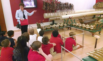 Students from Madison Heights enjoy a tour of the Musical Instrument Museum's Indonesia exhibit in the Asia Gallery, led by volunteer museum guide Phyllis Soben. The tour was sponsored by the Madison Education Foundation, a nonprofit organization created to expand music, fine arts, and drama within the Madison district (submitted photo).