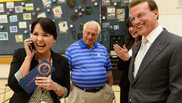 "Longview Elementary School TAP Master Teacher Ana Gutierrez, left, shares good news with her husband (""Honey, I just won $25,000!"") while Milken Family Foundation Chairman and Co-Founder Lowell Milken, right, and baseball legend and friend of the Milken Family Foundation Tommy Lasorda cheer her on (photo courtesy of Milken Family Foundation)."