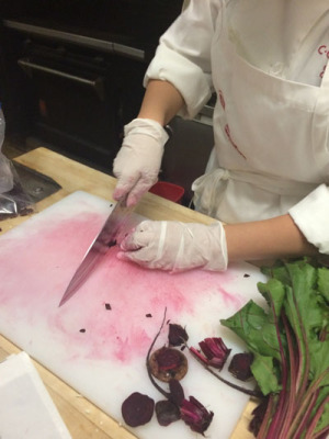 """A student from the Careers through Culinary Arts Program (C-CAP) trims and cuts a beet purchased by a shopper at the Saturday Uptown Farmers Market, as part of C-CAP's free """"Vegetable Valet"""" service (photo courtesy of Uptown Farmers Market)."""