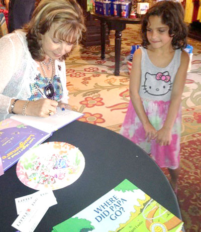 Children's author and Valley resident Judy Laufer signs a copy of one of her books for a little fan (submitted photo).