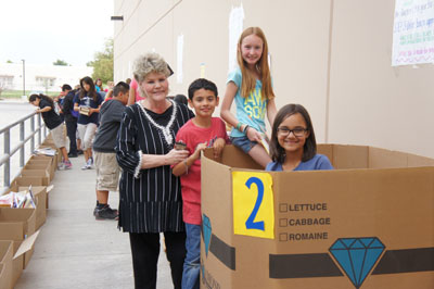 Susie Cook, superintendent of the Washington Elementary School District, visits with some students who were volunteering to help sort through more than 10,000 books donated to the district in March 2014 and collected through an in-store book drive hosted by all 117 Fry's grocery stores in Arizona and coordinated by BookPALS and Discover Books (photo by Teri Carnicelli).