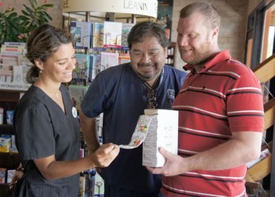 Theresa Stickler, owner and pharmacist at Melrose Pharmacy, demonstrates one of the new services offered to customer Jared Nations, right, and his partner Miguel Valverde, who himself is a pharmacy technician. Along with medication synchronization, which allows patients to have all their prescriptions refilled on the same day, Melrose Pharmacy also offers the MyOnePac box, in which a customer's medications come organized by date and time, securely sealed in easy-to-open packages. Each package shows everything a customer needs to take the right medications at the right time (photo by Teri Carnicelli).