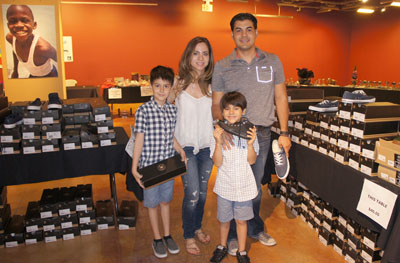 Taking advantage of the great footwear prices at the Global Family Philanthropy Pop-Up Shop last month at the Scottsdale Waterfront are the Castro family from Casa Grande, clockwise from left: Ricky, 9; Myriam; Ricardo; and Danny, 7. All proceeds benefited the Sunnyslope Youth Center (photo by Teri Carnicelli).