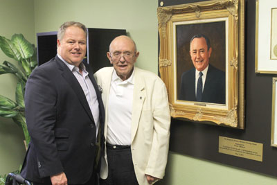 Tim O'Neal, CEO of Goodwill (left), congratulates longtime volunteer Dennis Mitchem on having one of the organization's conference rooms dedicated in his honor (submitted photo).