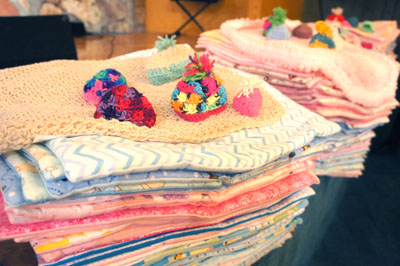 "Volunteers with Reap What You Sew created hundreds of small ""Angel Wraps"" and crocheted beanies for premature babies and newborns at various Valley hospitals (photo by Teri Carnicelli)."