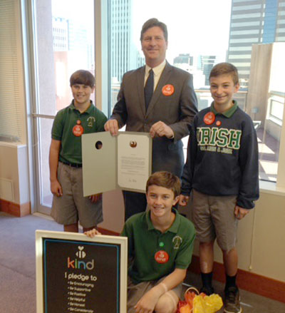 "Phoenix Mayor Greg Stanton presents a copy of the proclamation declaring Nov. 13, 2015 as ""Be Kind Phoenix Day"" to three North Central youth who won this past spring's Be Kind ""Creative Expression"" contest. They are, clockwise from left: St. Simon & Jude students Ben Prebil, 12, Eli Reed, 13, and Seamus Simmons, 13 (photo by Teri Carnicelli)."